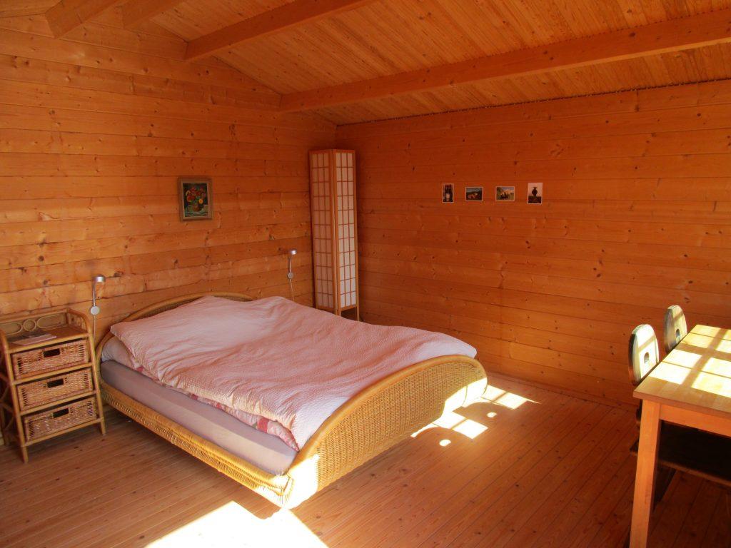 Pilgerhäusschen mit Doppelbett, Tisch und 2 Stühle, Sessel und Ständerlampe.
